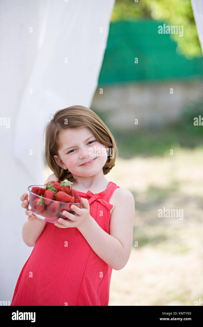Caucasian girl holding a bowl with nice strawberries - Stock Image