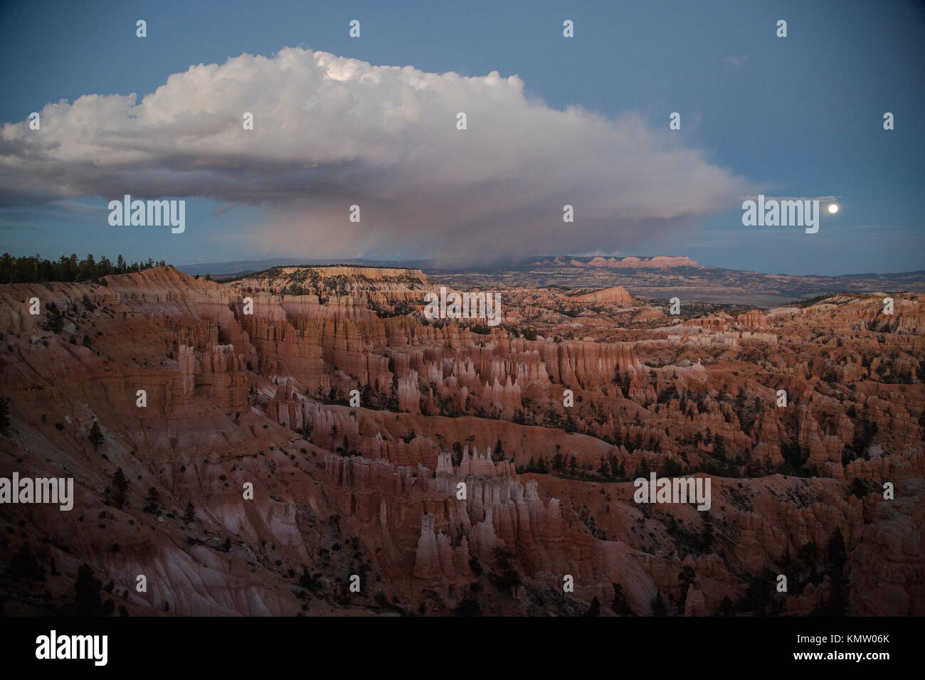 A view of Bryce Canyon with a storm cloud in the distance at dusk. - Stock Image