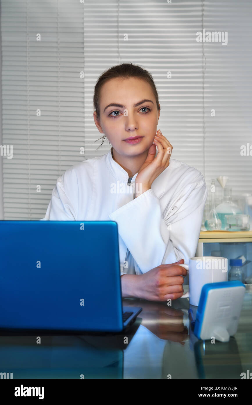 Young medtech, doctor or practitioner drinks coffee in front of working laptop in her office. - Stock Image