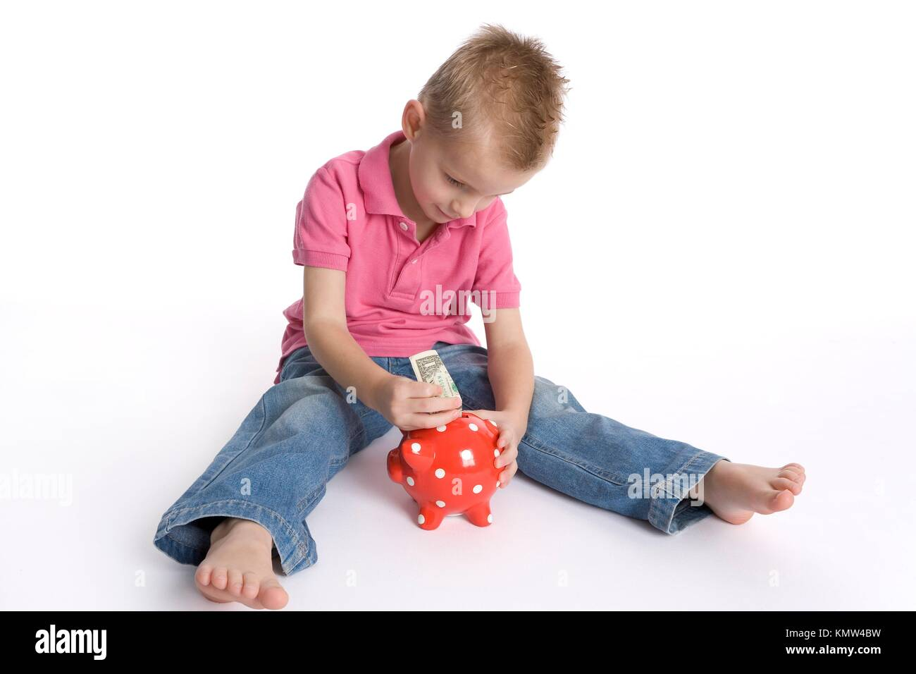 Little Boy Is Sitting On The Floor And Puts A Dollar Billet In A Piggy- Bank - Stock Image