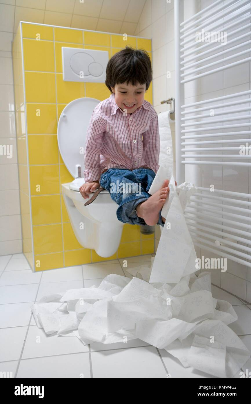 Little boy makes a mess with toilet paper in the bathroom - Stock Image