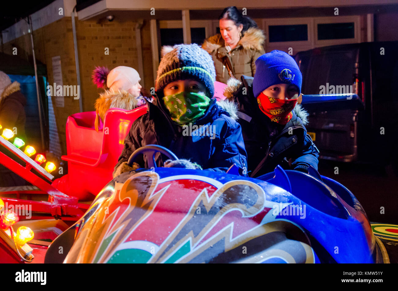 Two young brothers sit in a pod on a children's vortex style, spinning ride. - Stock Image