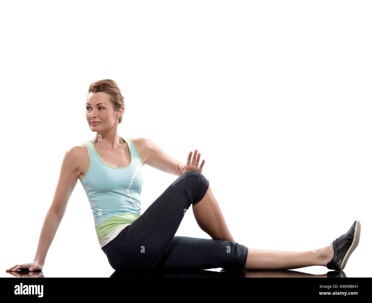woman on Abdominals rotation workout posture on white background  Sit up, straighten one leg and bend the other - Stock Image