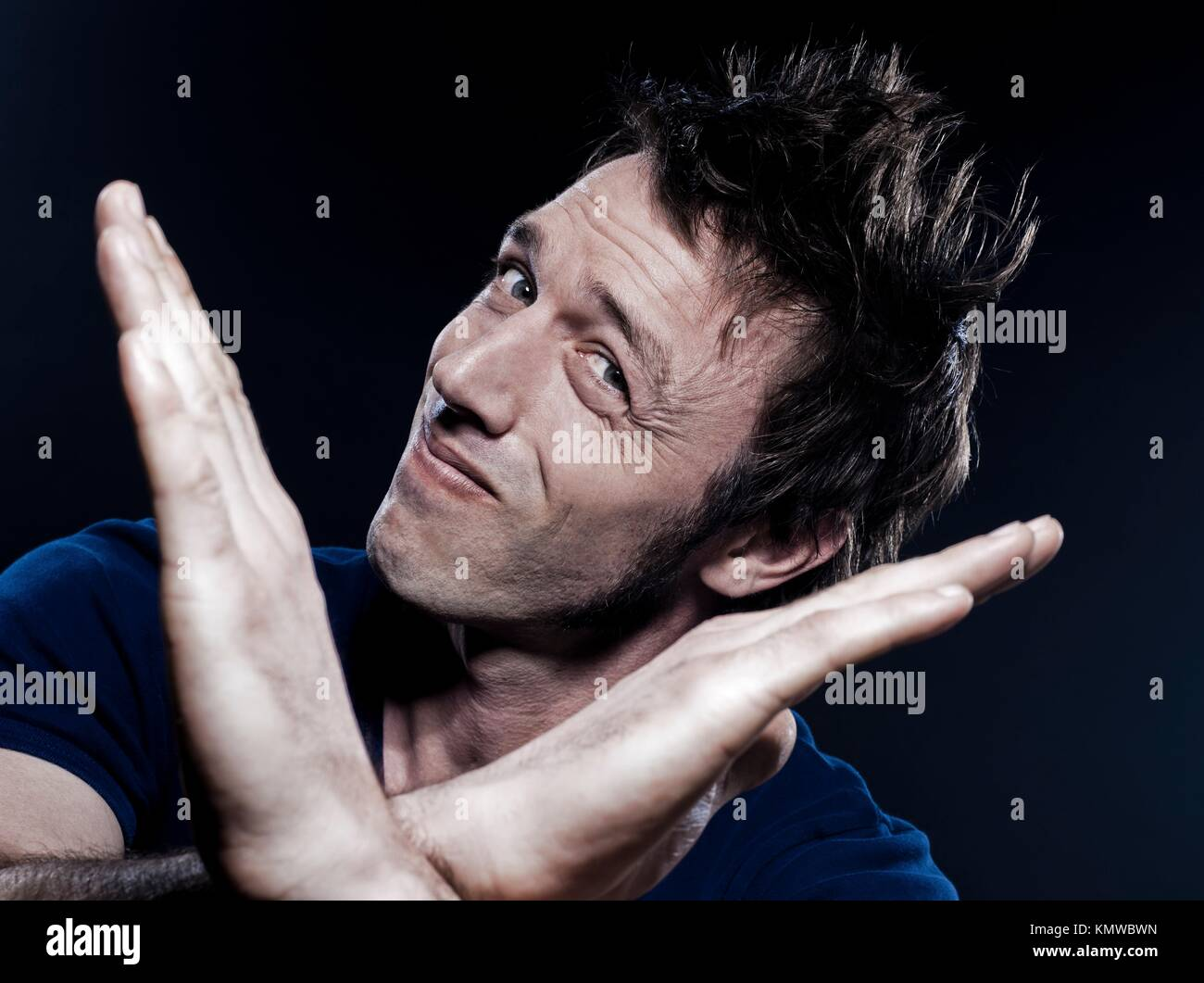 studio portrait on black background of a funny expressive caucasian man time out pause gesturing - Stock Image