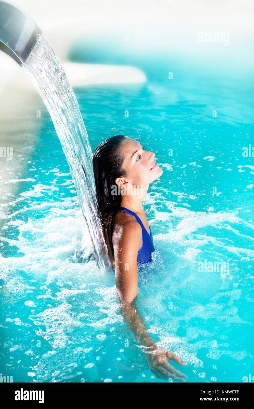spa hydrotherapy woman waterfall jet turquoise swimming pool water - Stock Image