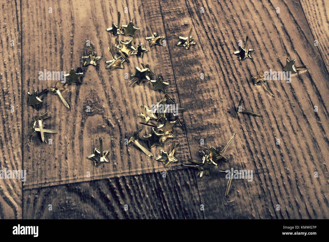close up of vintage abstract background of gold stars, fasteners, laying on wood grain floor - Stock Image