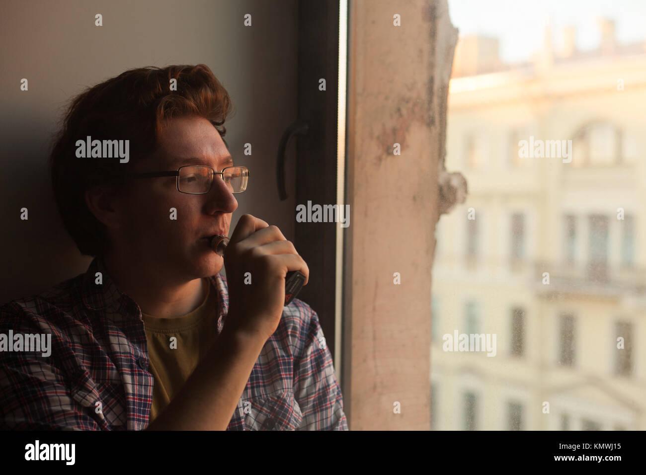 Young man smoking electronic cigarette near window. vaping. - Stock Image