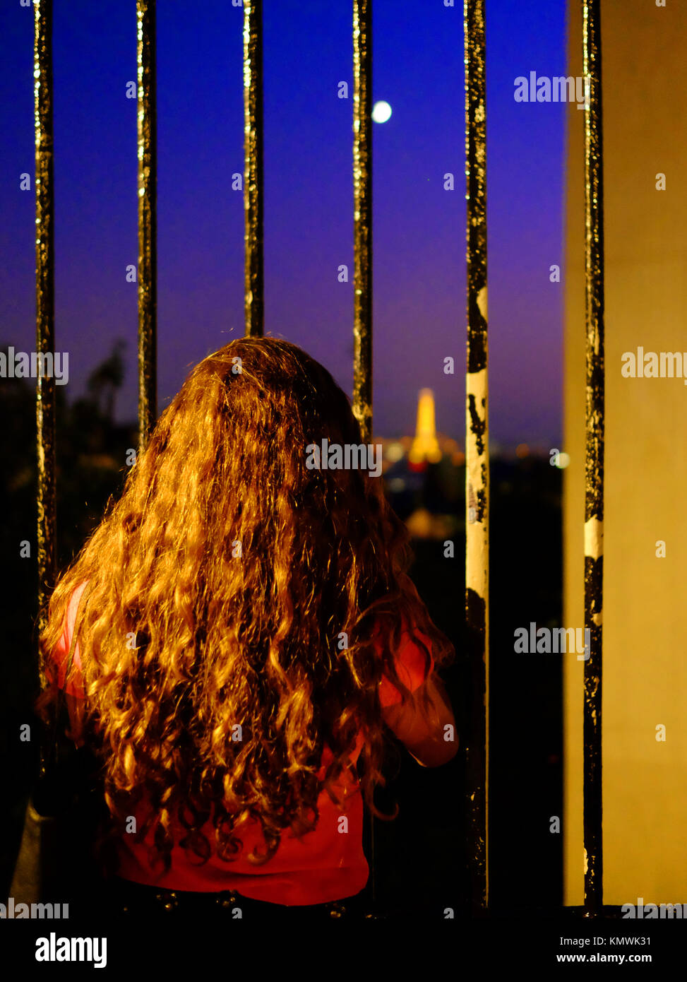 A young girl with very long hair gazes at the Eiffel Tower and the moon through railings in Montmartre in Paris, - Stock Image