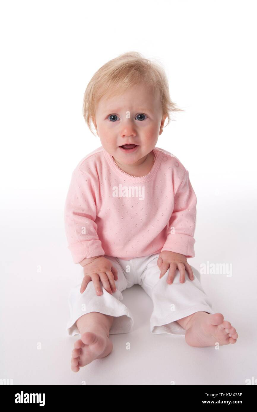 Baby Girl Is Sitting On The Floor With a disagreeing expression Stock Photo