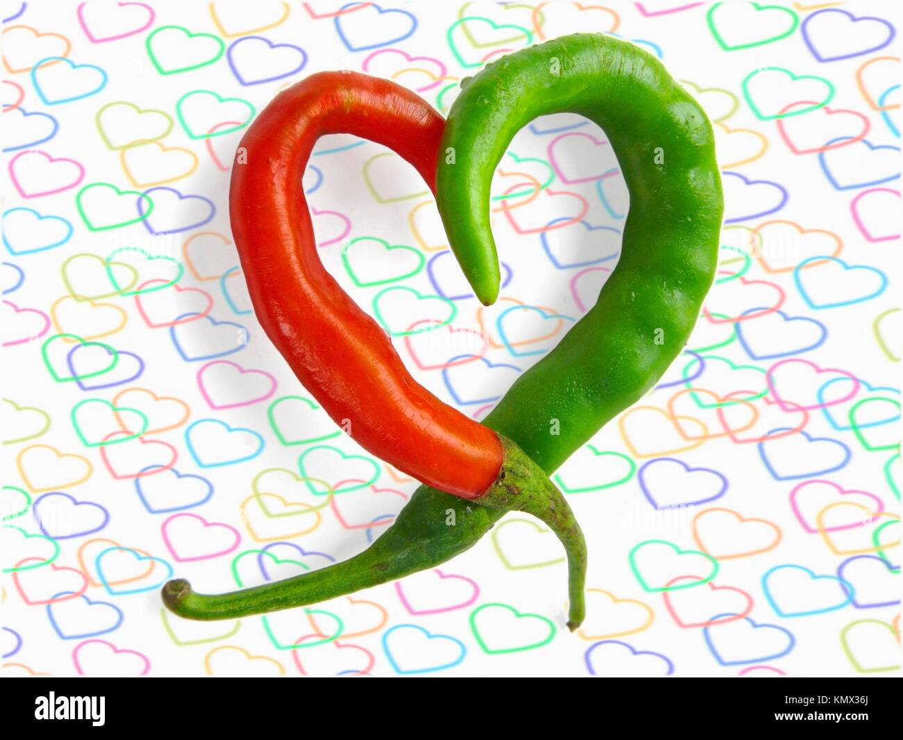Common Chili, Capsicum annuum, Red and green chilies are kept in heart shape - Stock Image