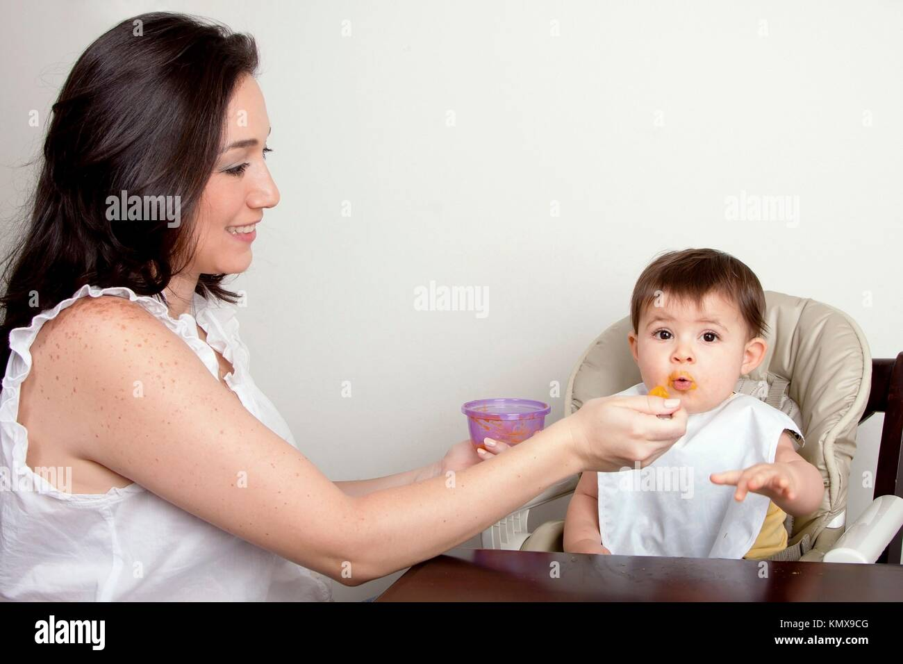 Beautiful happy mother or nanny feeds funny baby boy girl orange puree with spoon, infant eats messy, while sitting - Stock Image