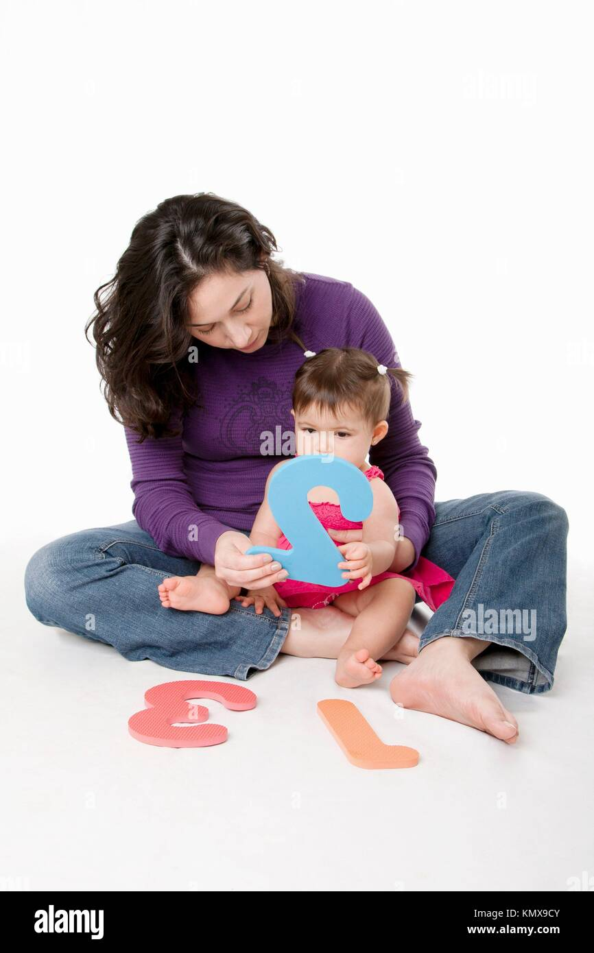 Mother, nanny, or teacher teaching baby to learn how to count one, two, three, with numbers in a playful way, while - Stock Image