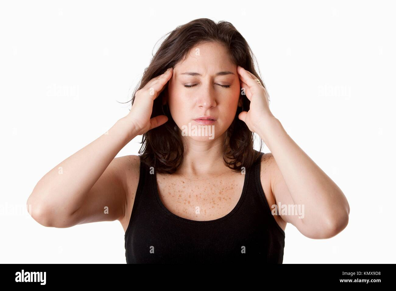 Face of beautiful young attractive woman with headcahe migraine unwell expression feeling sick, holding her head, - Stock Image