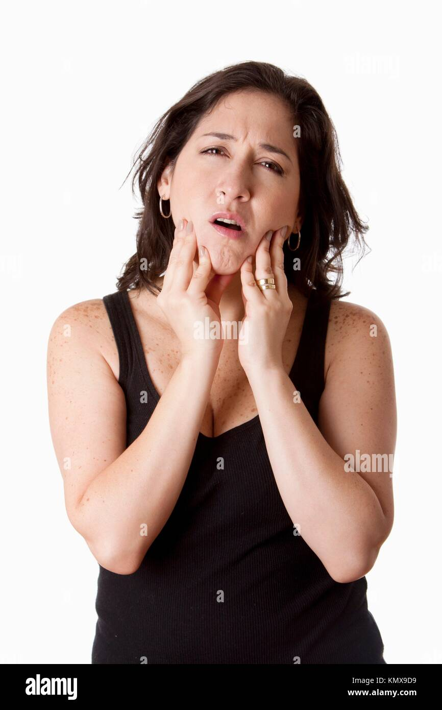 Beautiful young attractive woman with dental tooth jaw pain expression feeling unwell, holding her chin, isolated - Stock Image