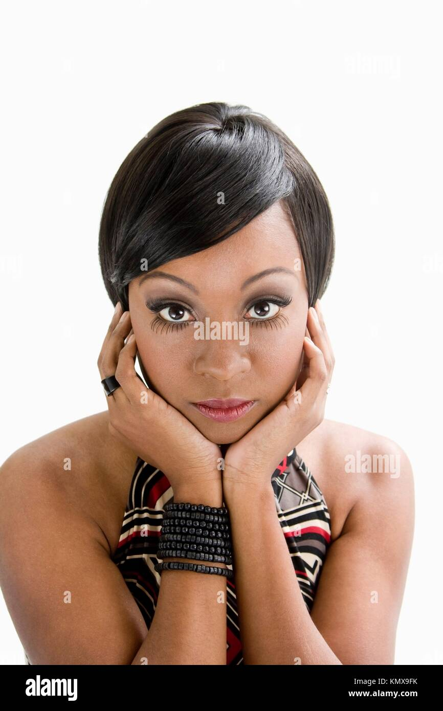 Beautiful African woman with huge eyes seventies style and hands to support face, isolated - Stock Image