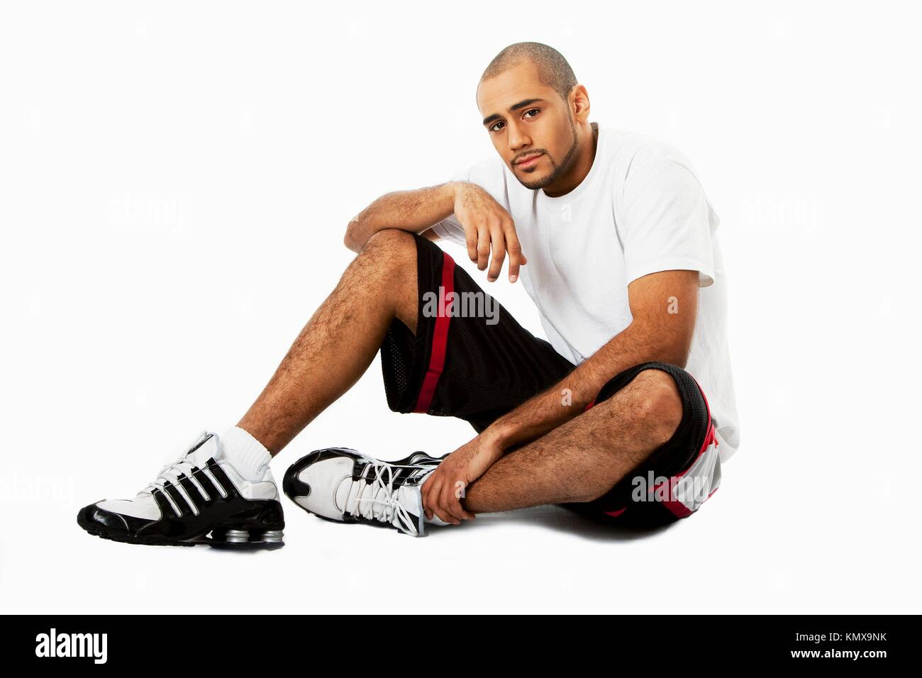 Sporty handsome African Hispanic guy sitting on floor, isolated - Stock Image