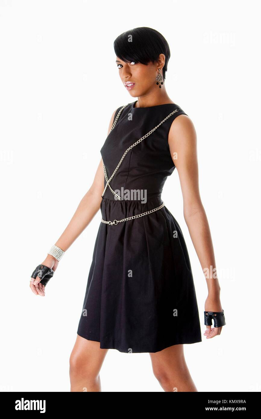 Beautiful modern classy African American female fashion model in black dress with silver chains and black biker - Stock Image