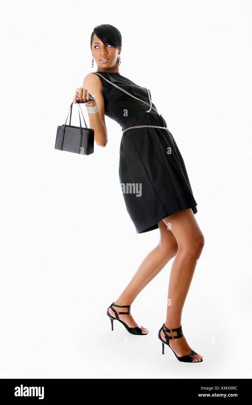 Beautiful modern classy African American female fashion model in black dress with silver chains, black purse and - Stock Image