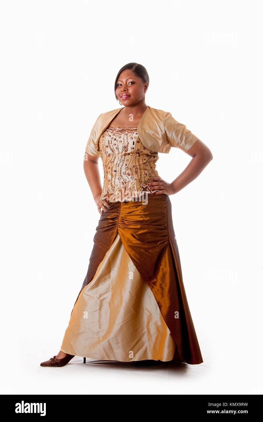 Beautiful African American woman in brown with gold dress, hands on hips and standing, isolated - Stock Image