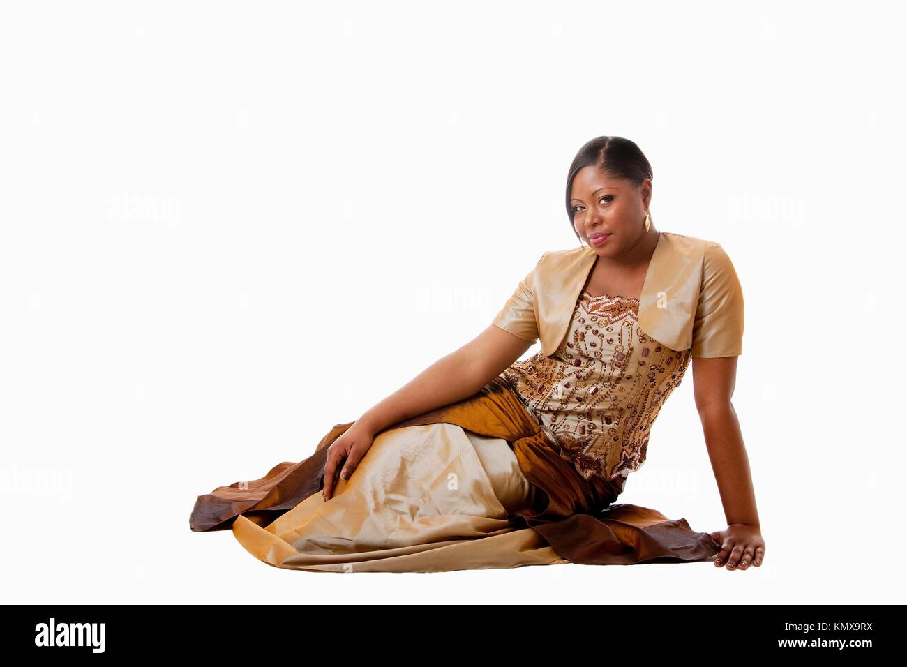 Beautiful African American woman in brown with gold dress, sitting laying on floor, isolated - Stock Image