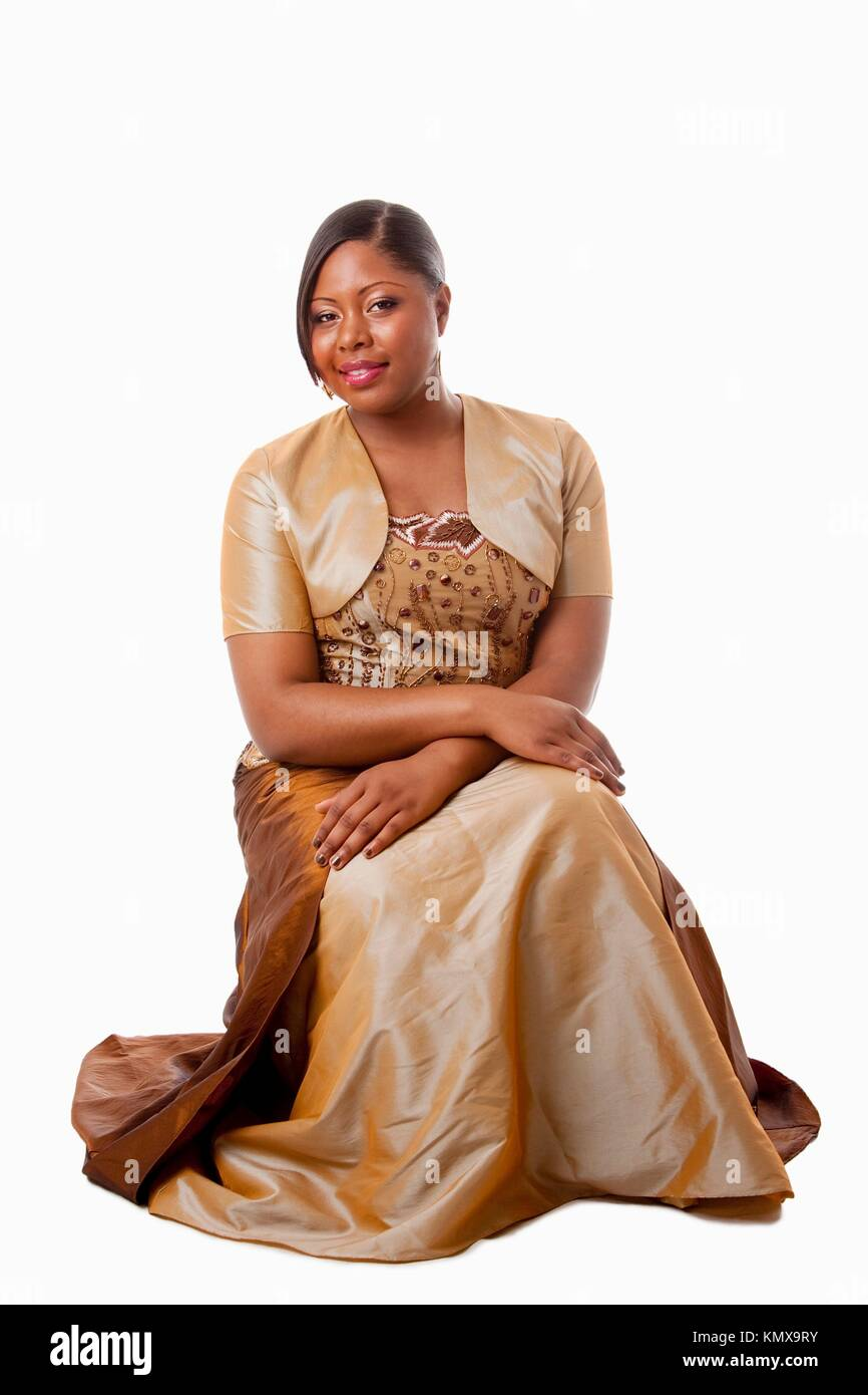 Beautiful African American woman in brown with gold dress, sitting, isolated - Stock Image