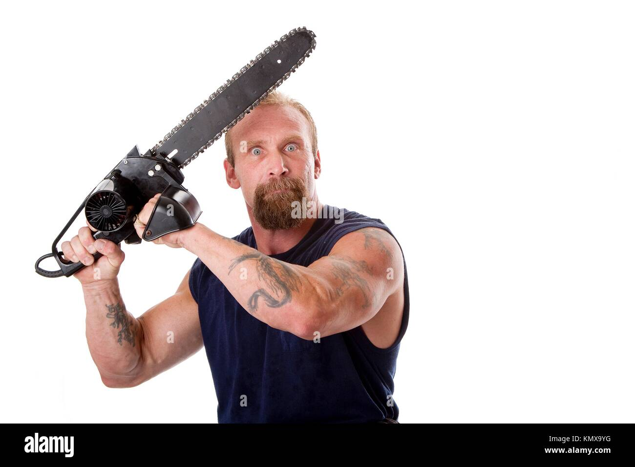 Crazy Caucasian man with tattoos and chainsaw above his head with strong expression in eyes, isolated Stock Photo