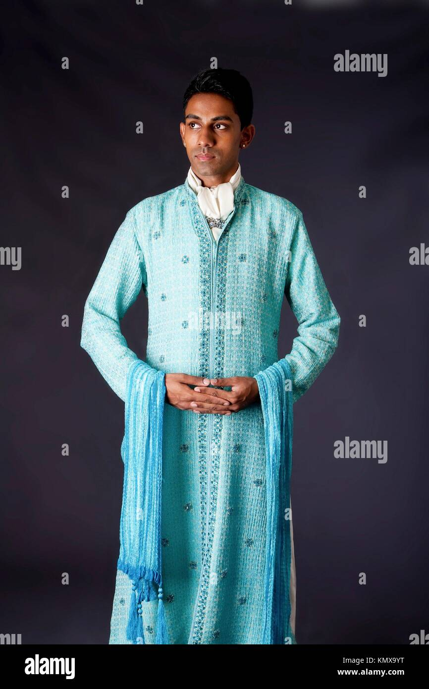 Beautiful authentic Indian hindu man in typical ethnic groom attire standing with hands together  Bangali male wearing - Stock Image