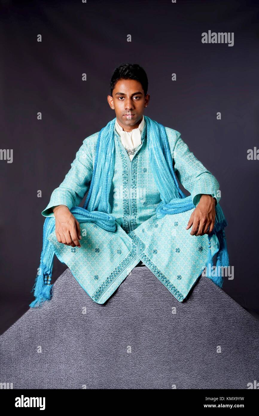 Beautiful authentic Indian hindu man in typical ethnic groom attire sitting in lotus position with legs crossed - Stock Image