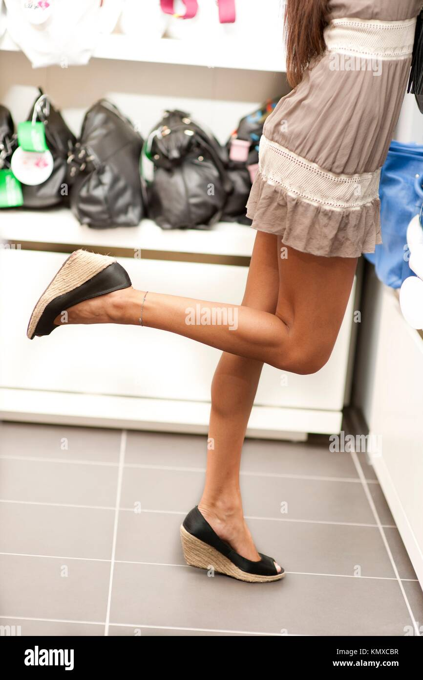 Shopping girls on tiptoe, trying to take bags on shelves - Stock Image