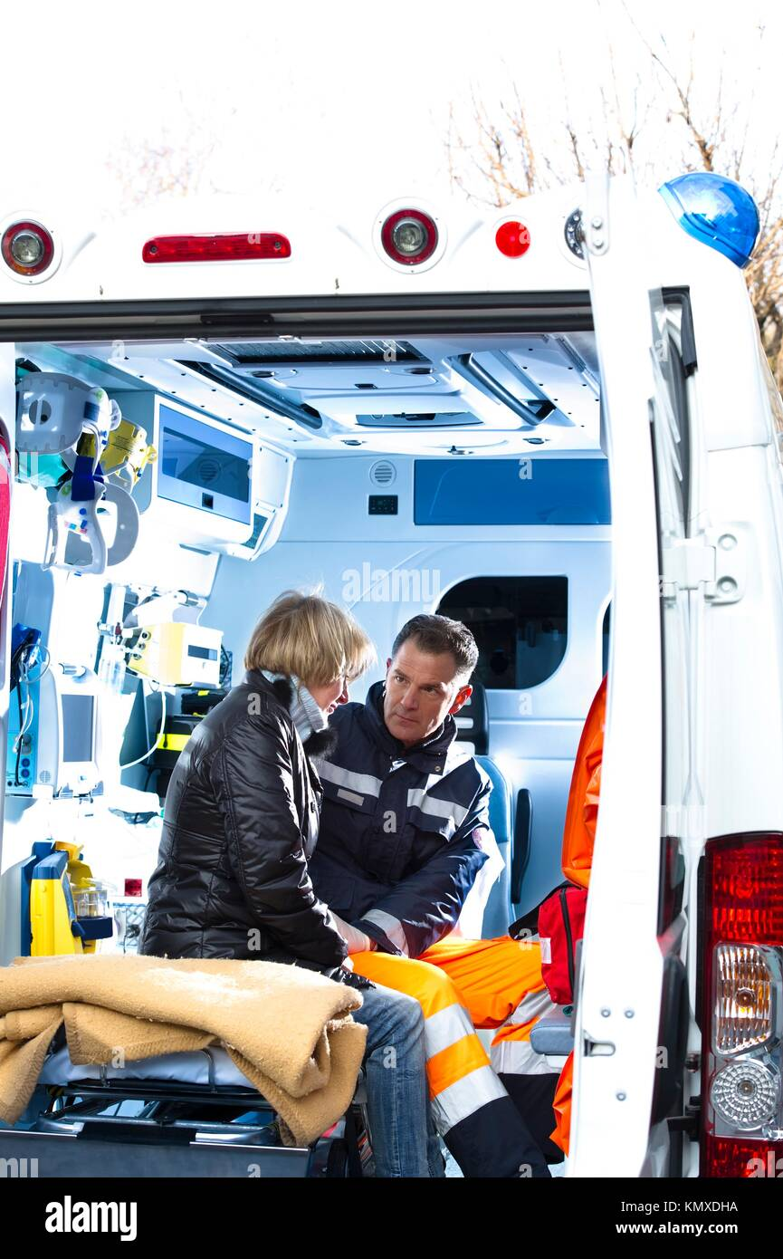 Male Paramedic Assistting Injured Woman - Stock Image