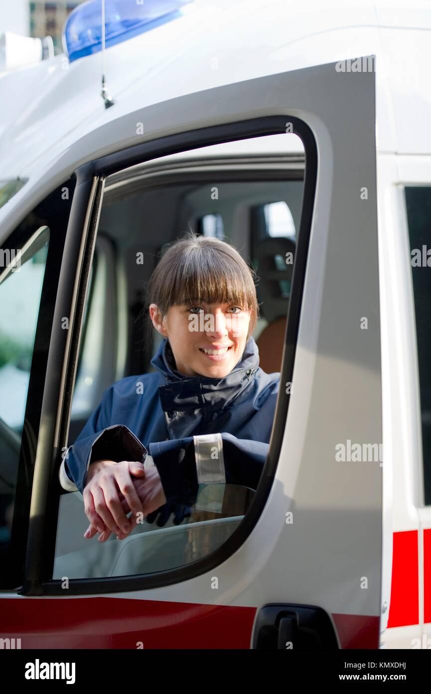 Female Paramedic Driving Ambulance - Stock Image