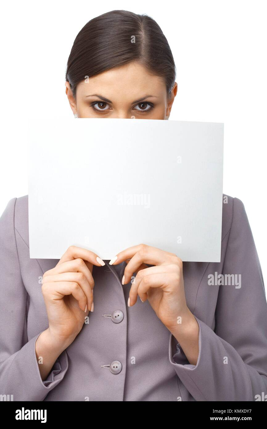 Closeup portrait of a young girl hiding behind an empty white billboard , isolated on white - Stock Image