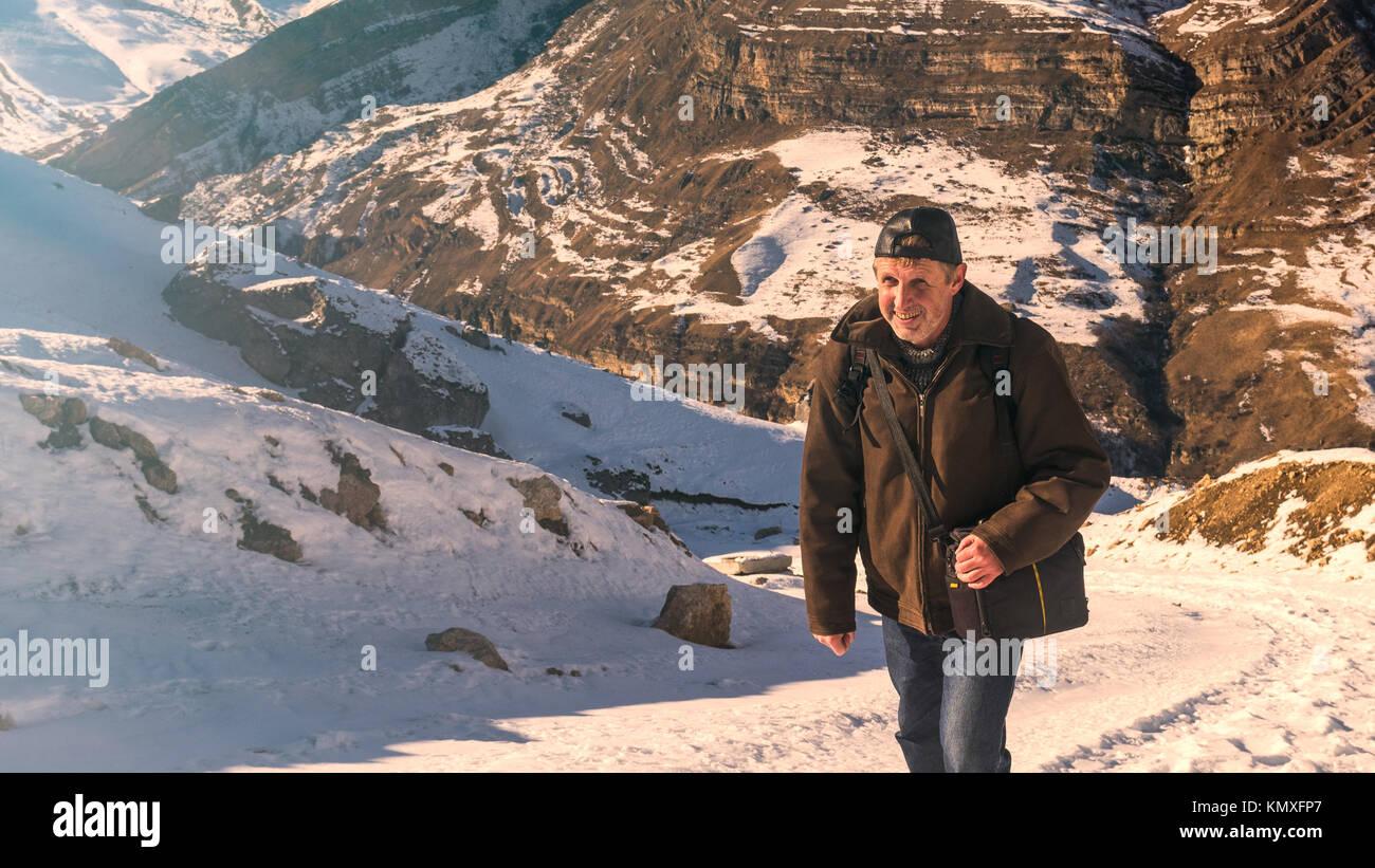 Tourist climber on a mountain snow trail Stock Photo