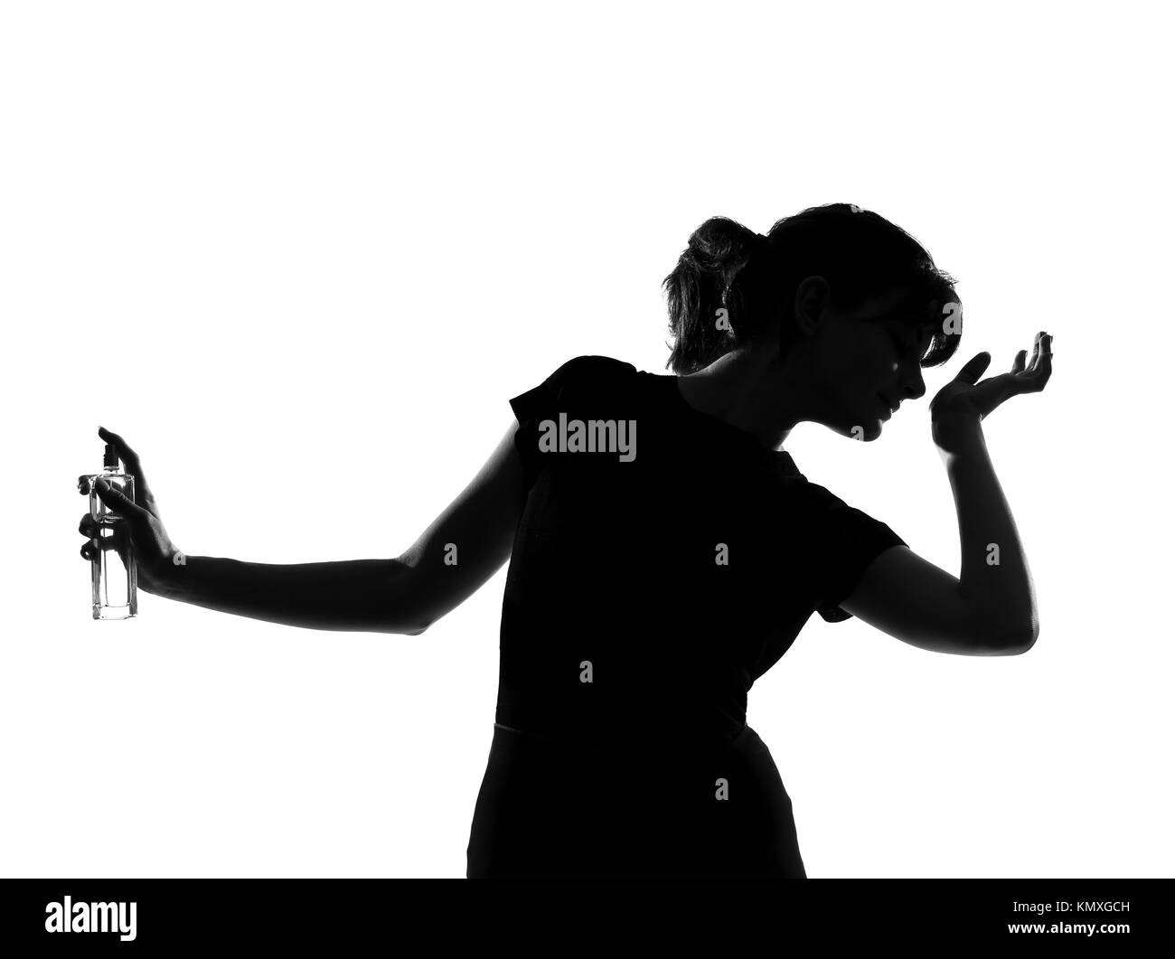 portrait silhouette in shadow of a young woman smelling perfume in studio on white background isolated - Stock Image