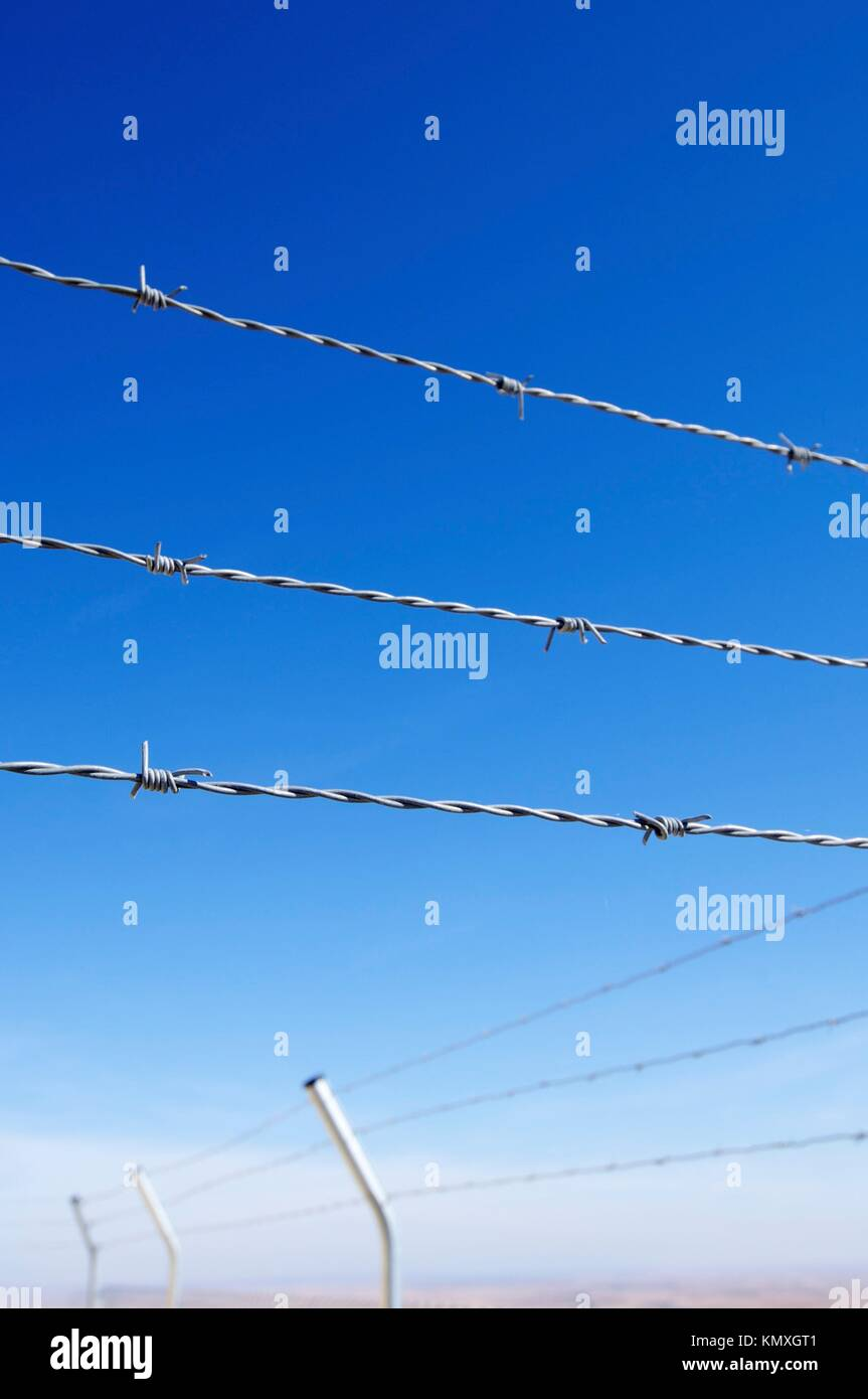 foreground of a barbed wire fence on a clear day - Stock Image