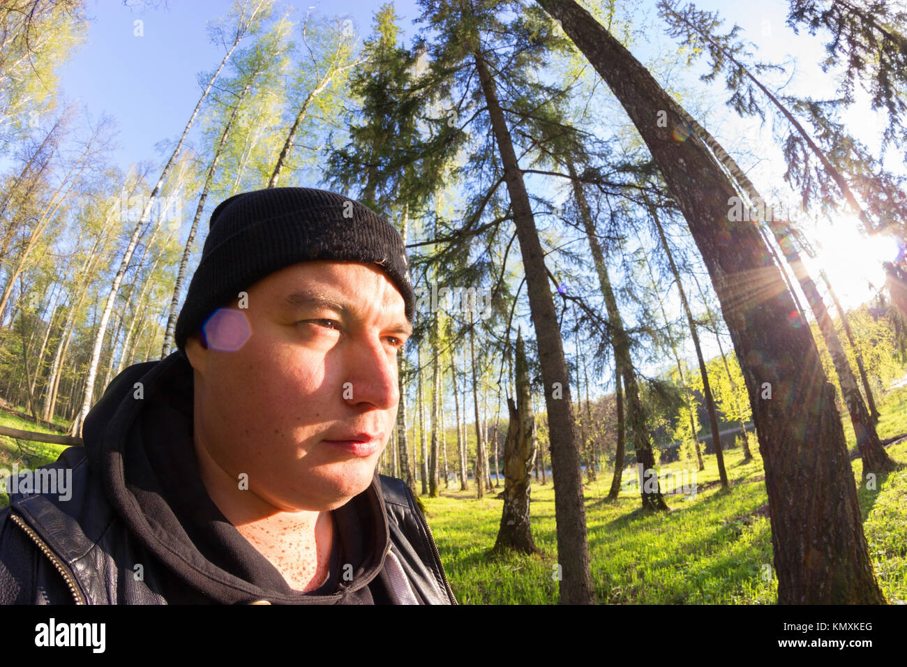 forester in black clothes going through the forest Stock Photo