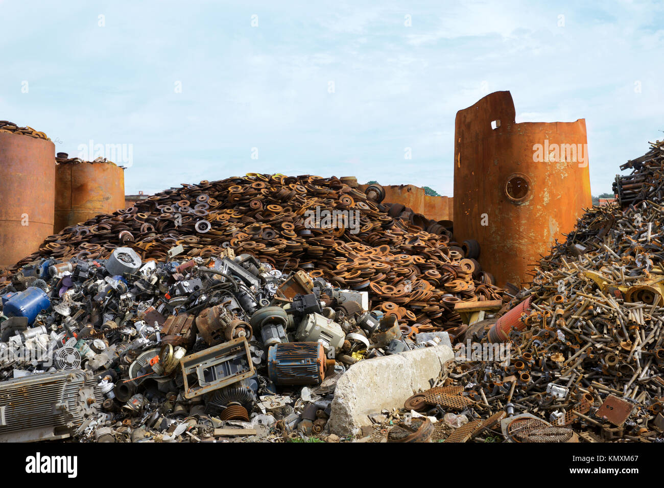 recycling center  with bales of metal and crane with claw tossing truck  and rusty wheels - Stock Image