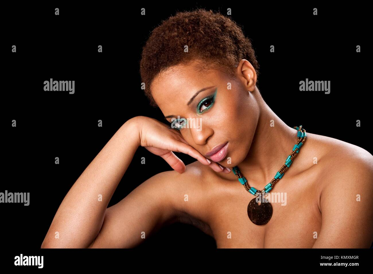 Beautiful face of an African American female fashion model with bare shoulders, eyelids with green eyeshadow and - Stock Image
