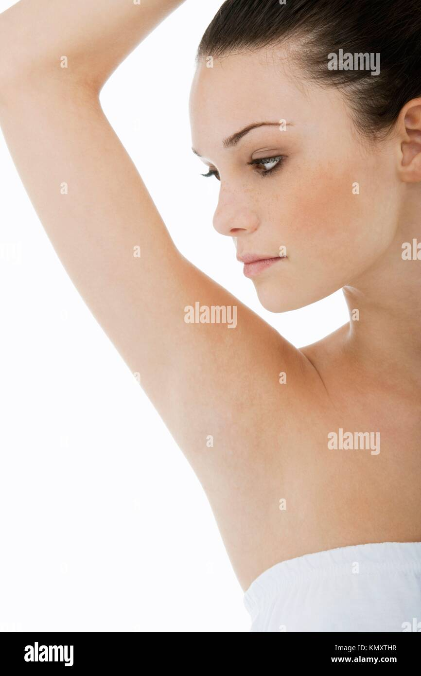 Young woman looking at her clean armpit - Stock Image