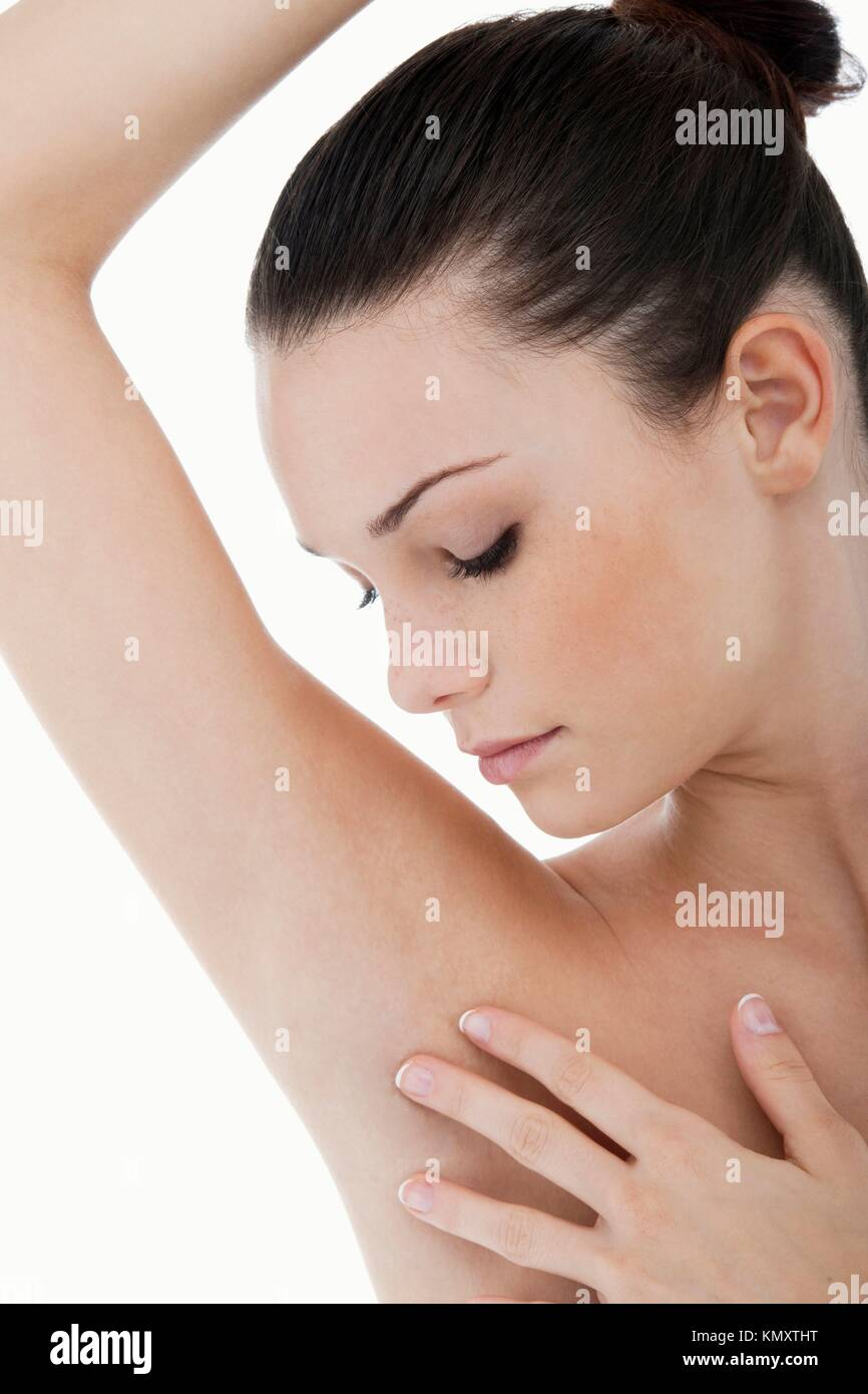Young woman stroking her clean armpit - Stock Image
