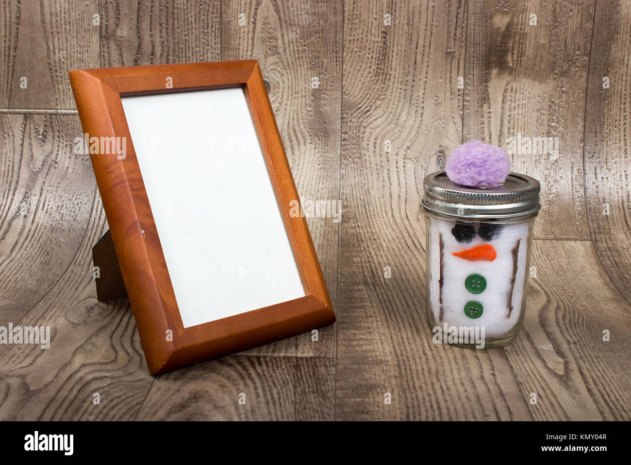 background of empty wooden  picture frame setting a wooden shelf with a hand crafted snowman made with twigs, buttons, - Stock Image