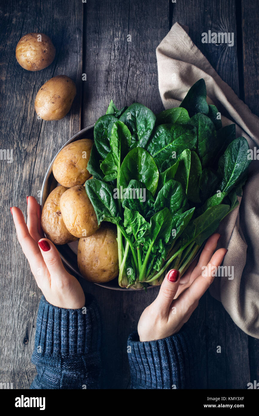 Woman holding plate with potatoes and fresh spinach on rustic wooden background in the kitchen - Stock Image