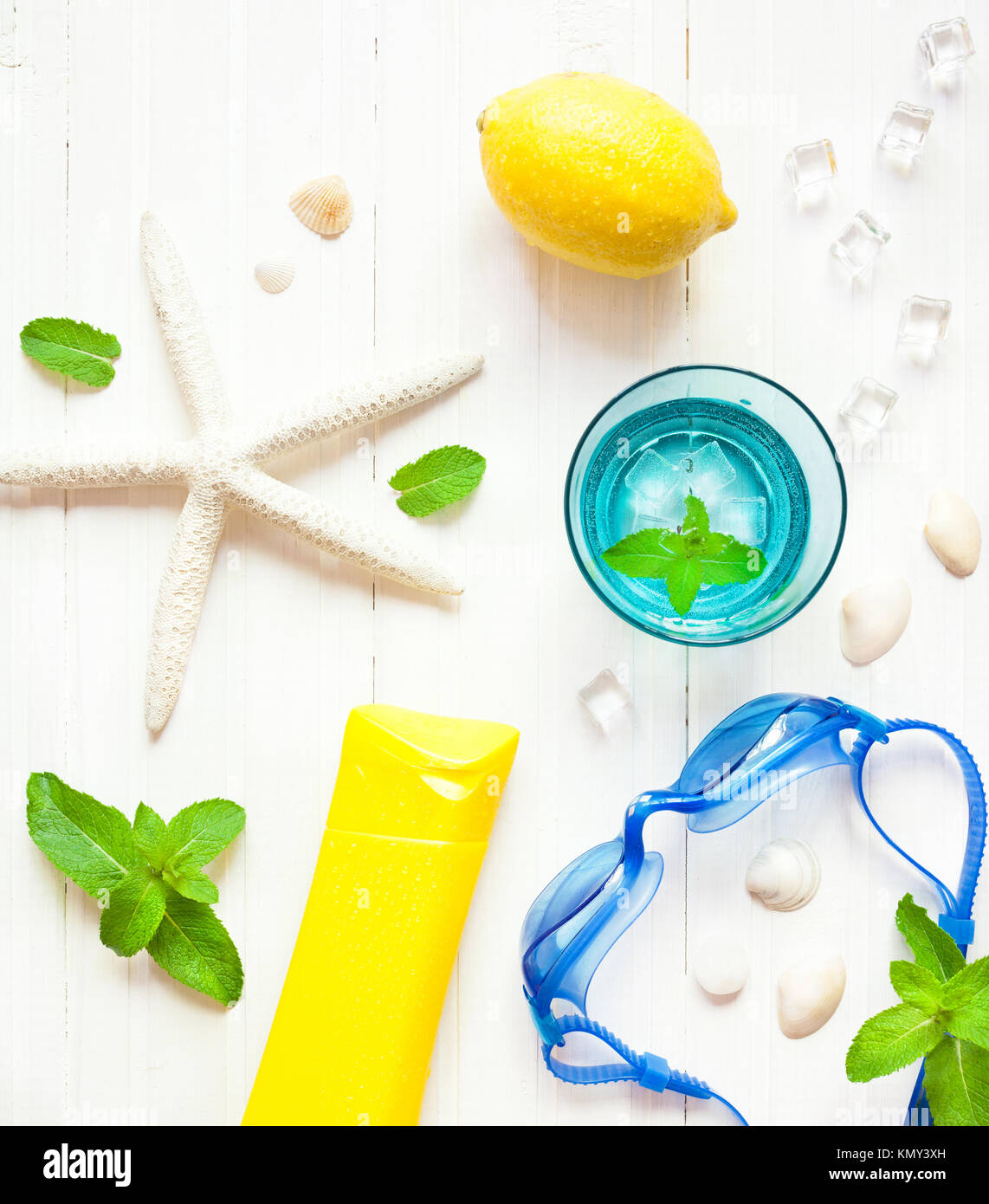 Summer flatlay with watersport goggles, mint cold mojito and sea star on the white table - Stock Image