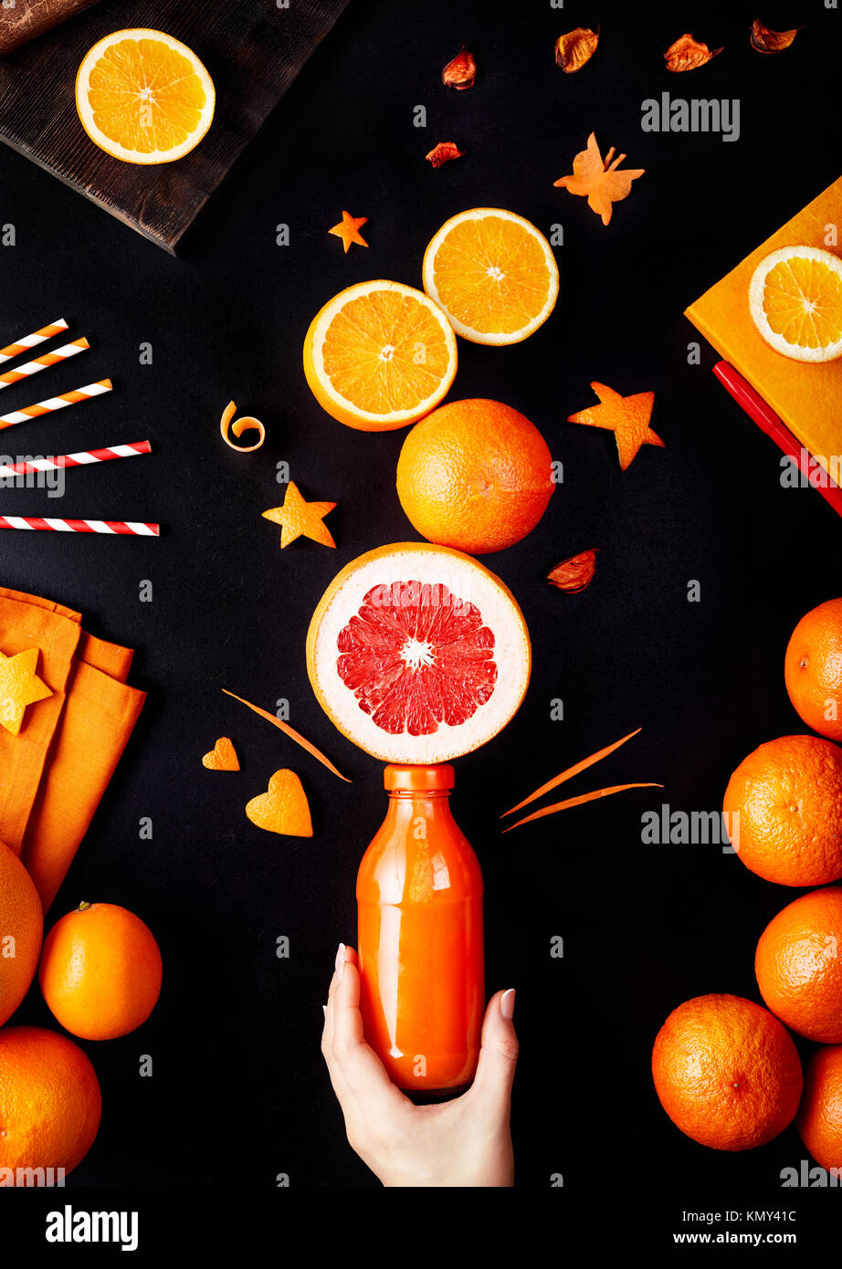 Fresh detox juice from oranges, grapefruit and lemon on black background flay lay - Stock Image