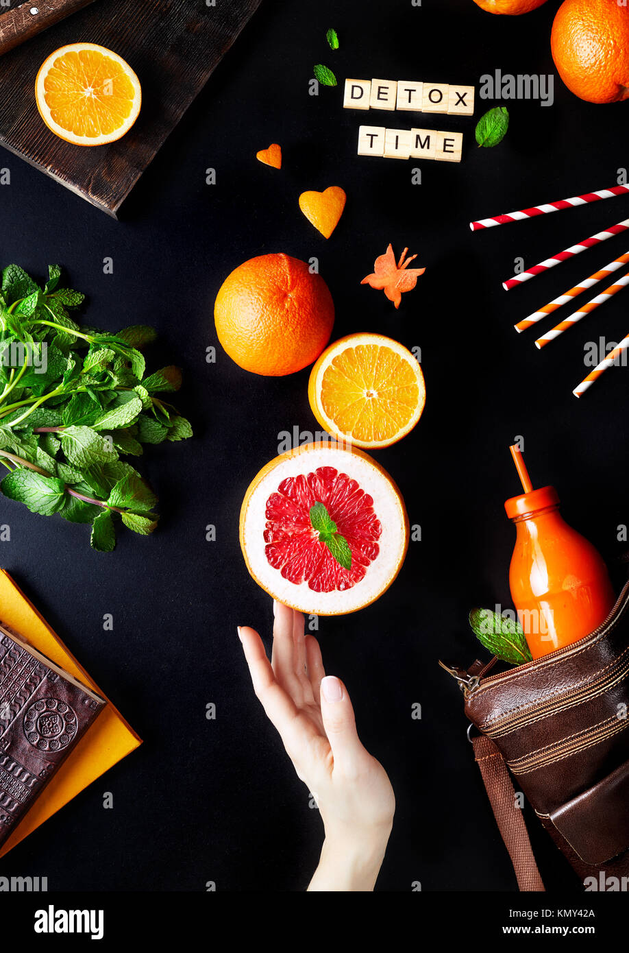 Fresh detox juice from citrus on black background flay lay - Stock Image
