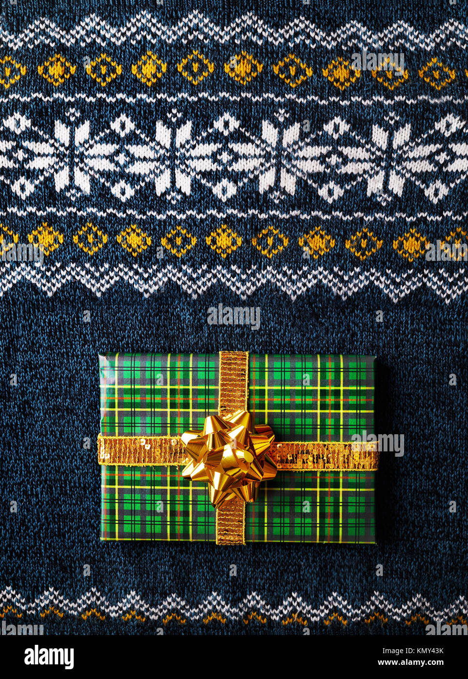 Green wrapped present with golden bow on man sweater at Christmas time - Stock Image