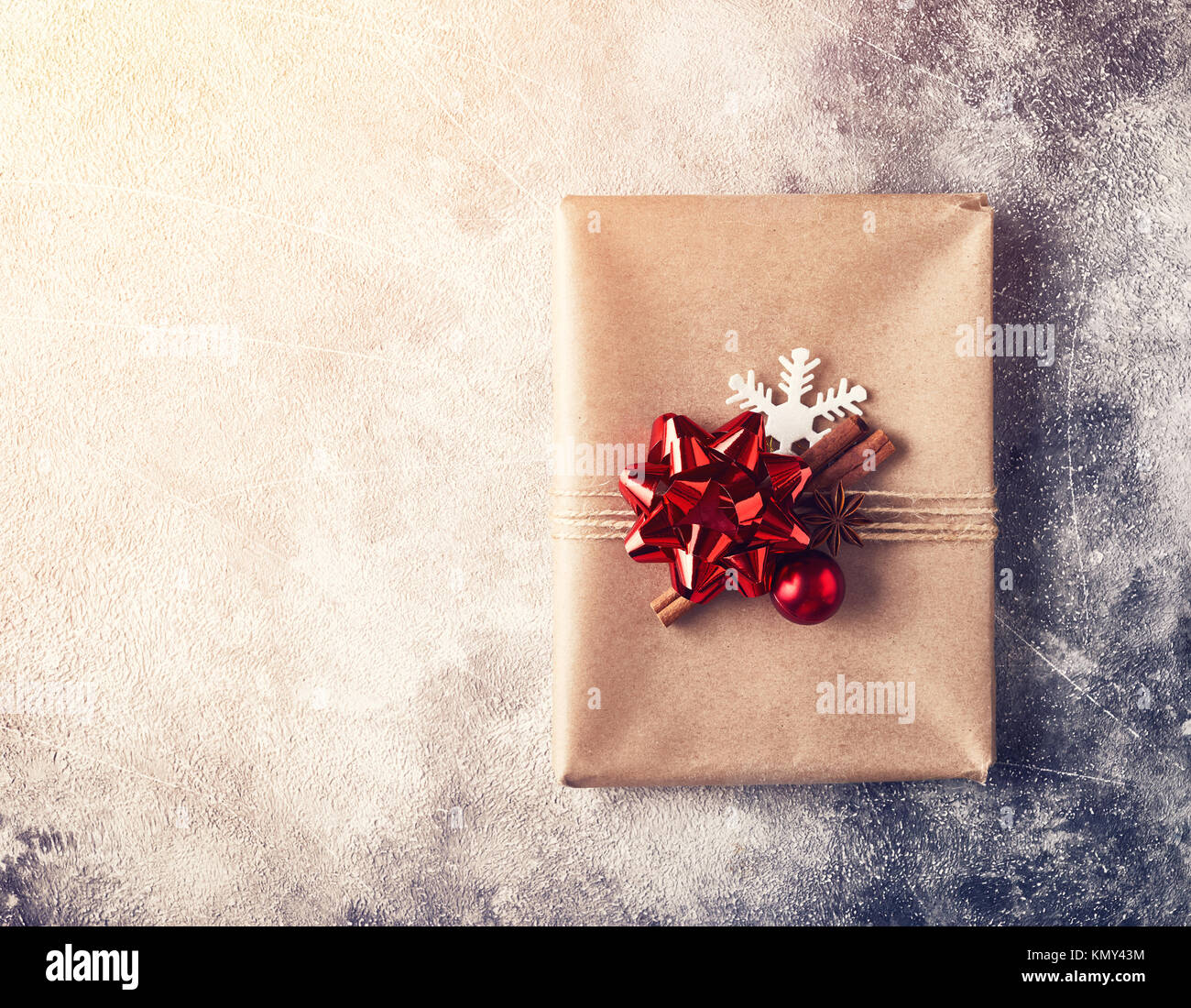 Wrapped present with red bow on textured winter background - Stock Image