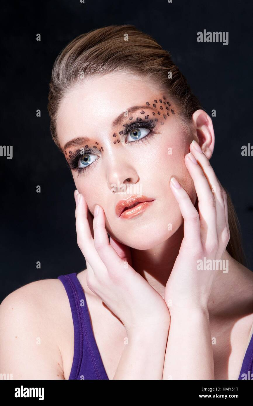 Tilted face of a beautiful dirty-blond girl with leopard print eyeshadow, isolated - Stock Image