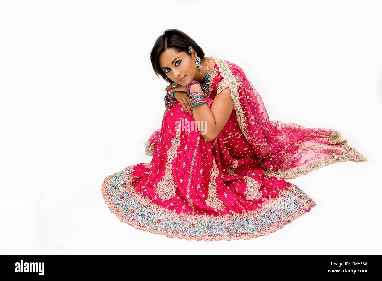 Beautiful Bangali bride in colorful dress sitting, isolated - Stock Image