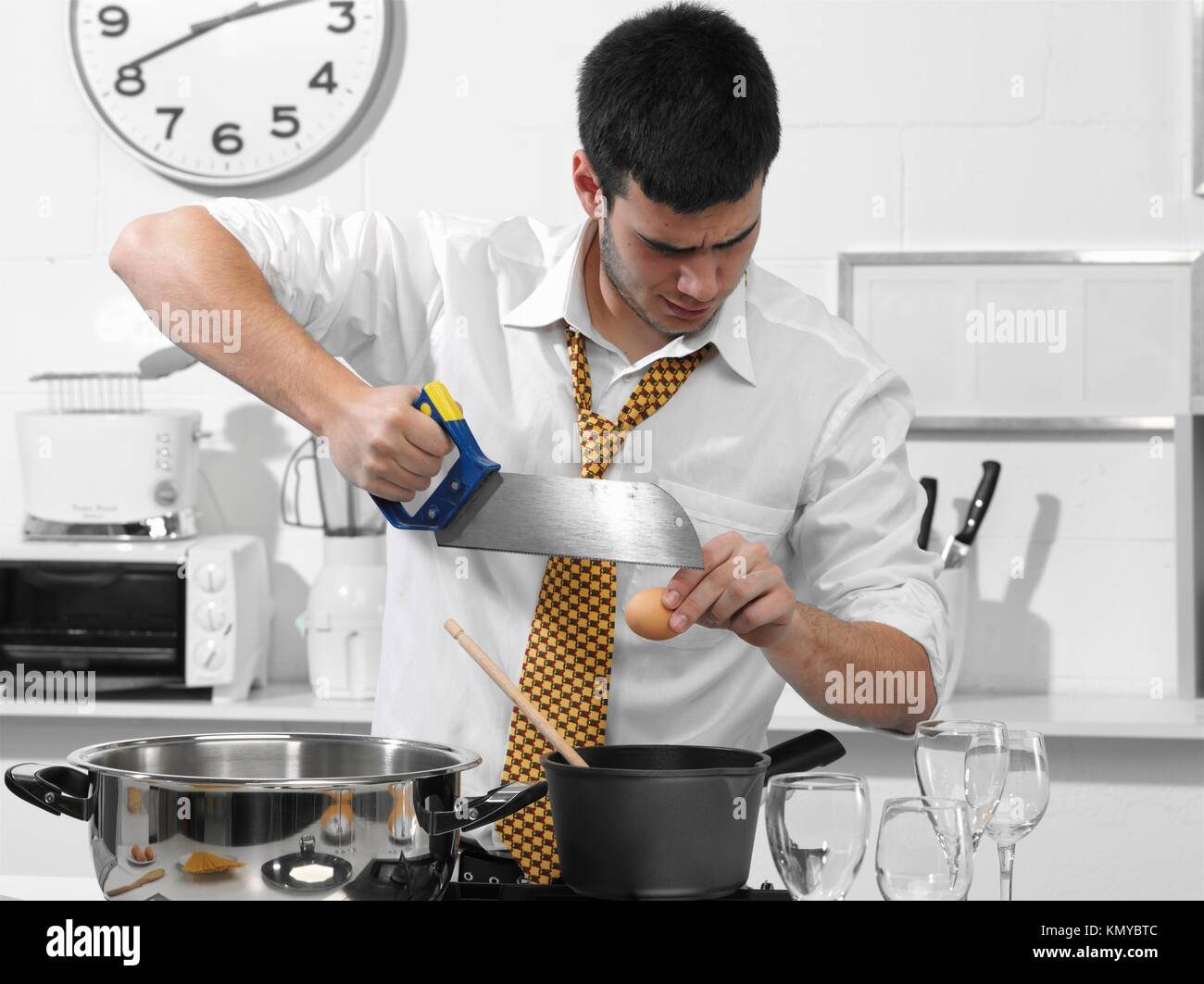 Business Man In The Kitchen Cutting An Egg With A Saw Stock Photo Alamy